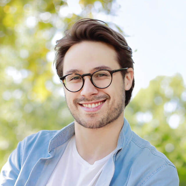 Smiling man wearing glasses and a denim shirt.jpg