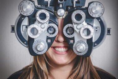 Woman enjoying eye exam, behind phoropter