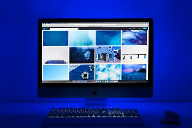 silver-imac-turned-on-displaying-different-photos-1999463