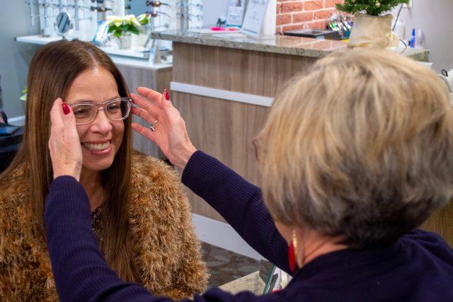 optician smiling patient glasses