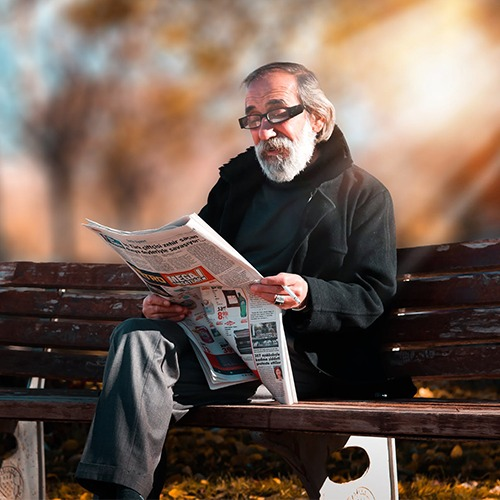 Man reading news paper on a bench