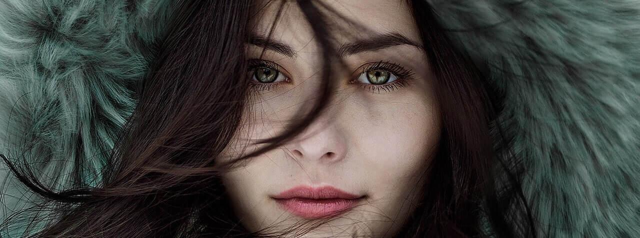 woman furry hat green eyes min