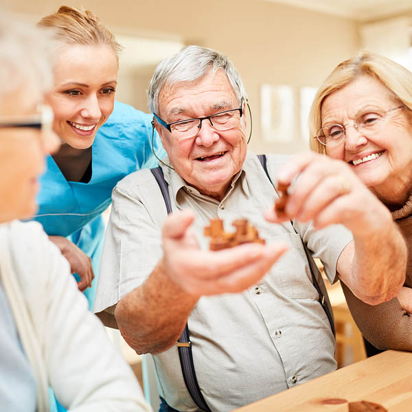 Group of seniors with dementia playing with a wooden puzzle in n