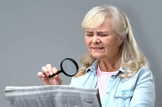 low vision patient using a magnifying glass