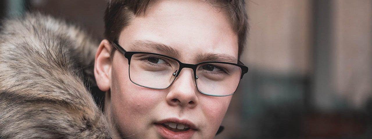 boy with glasses winter coat 1280x853