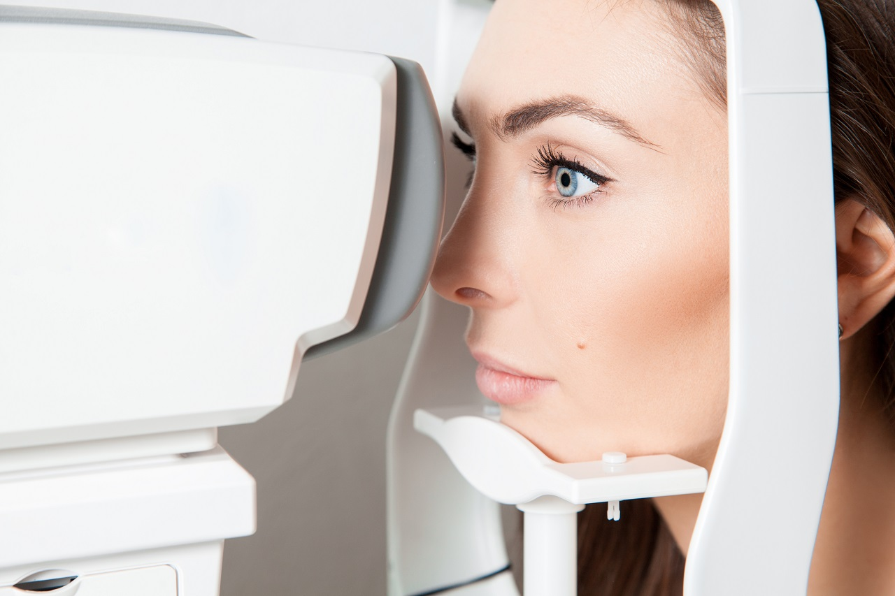 Sweet young adult brunette looking at eye test machine in ophtha
