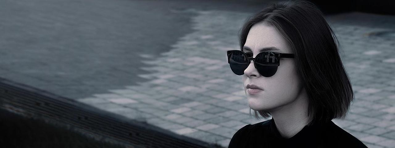 woman modeling black sunglasses