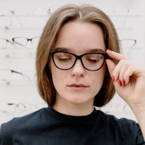 girl trying on a new pair of eyeglasses 640x640 1 300x300