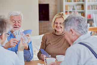 Senior retired friends play cards in their spare time or at reti