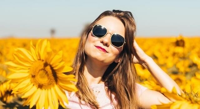 woman wearing sunglasses in field of sunflowers 640