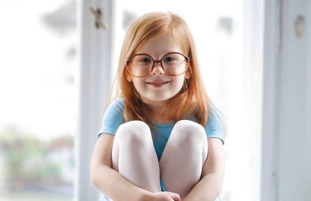 child girl redhead smiling glasses blue ballet dress 1000px