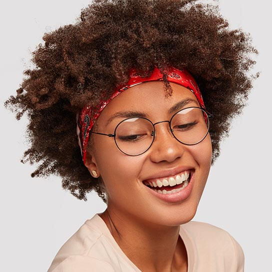 Charismatic Happy Black Curly Young Lady Looks Down With Broad S