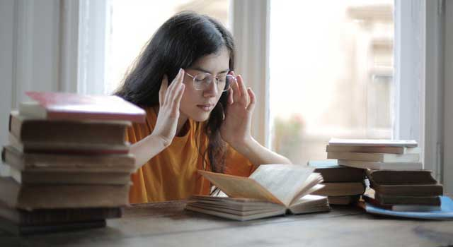 female-student-suffering-from-headache-in-library-3808057