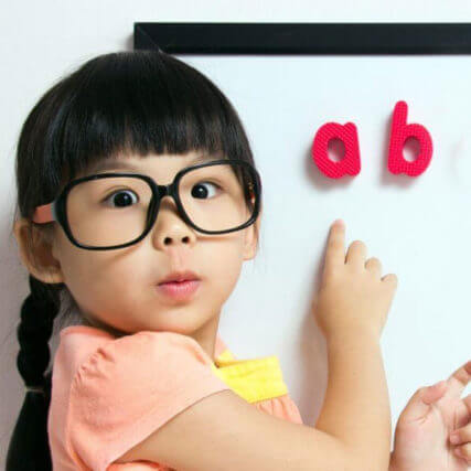 Girls wearing glasses pointing to letters on a whiteboard