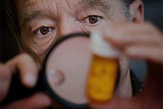 Man Examining Instructions On Medicine Bottle