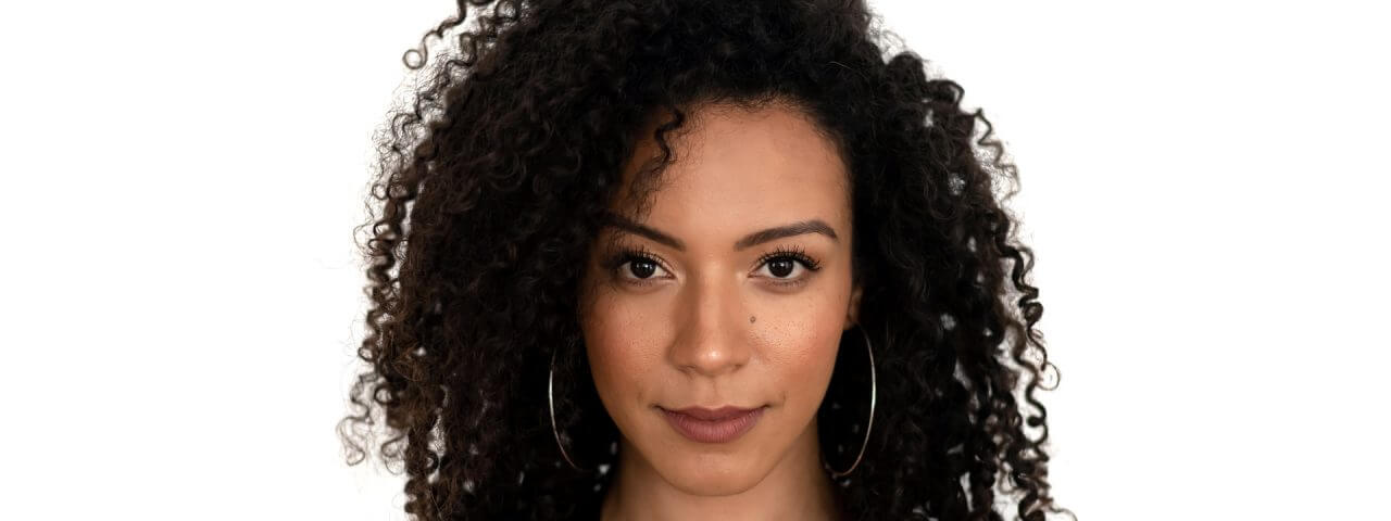 Isolated portrait of a latin woman with curly hair dressed in black