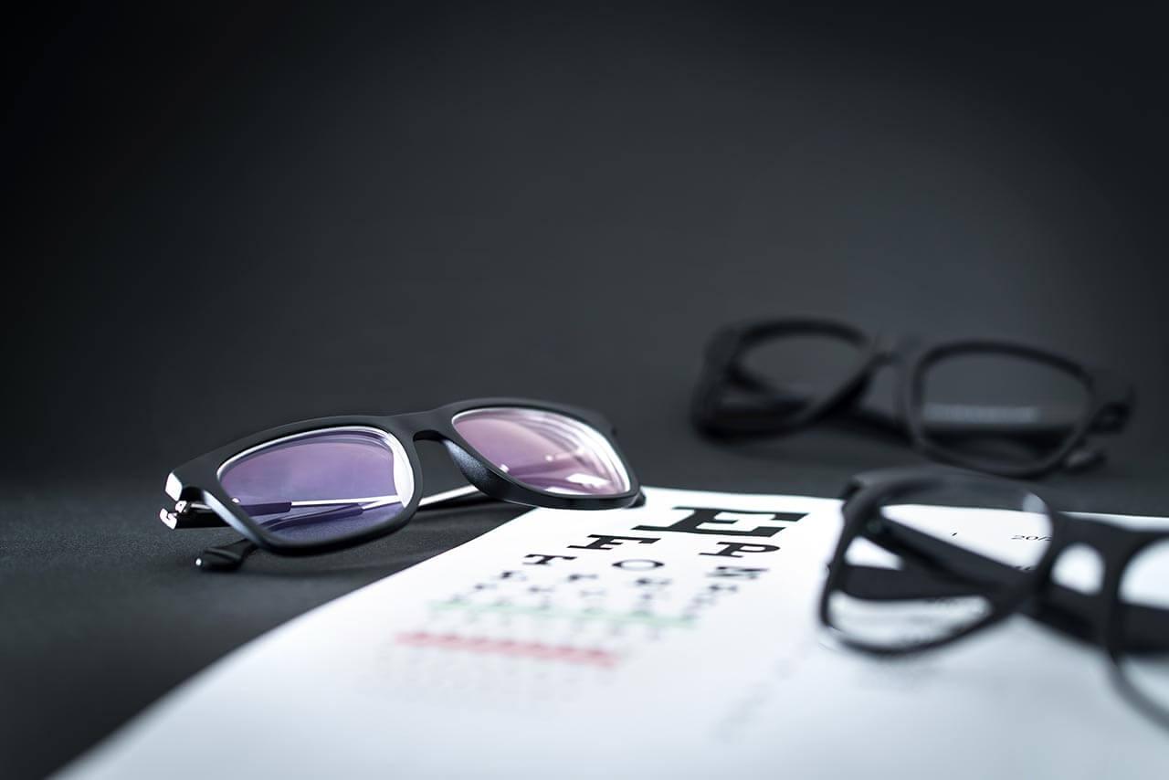 eyeglasses on top of eye chart