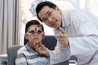 An Asian Ophthalmologist Examines The Childs Vision. An Optomet