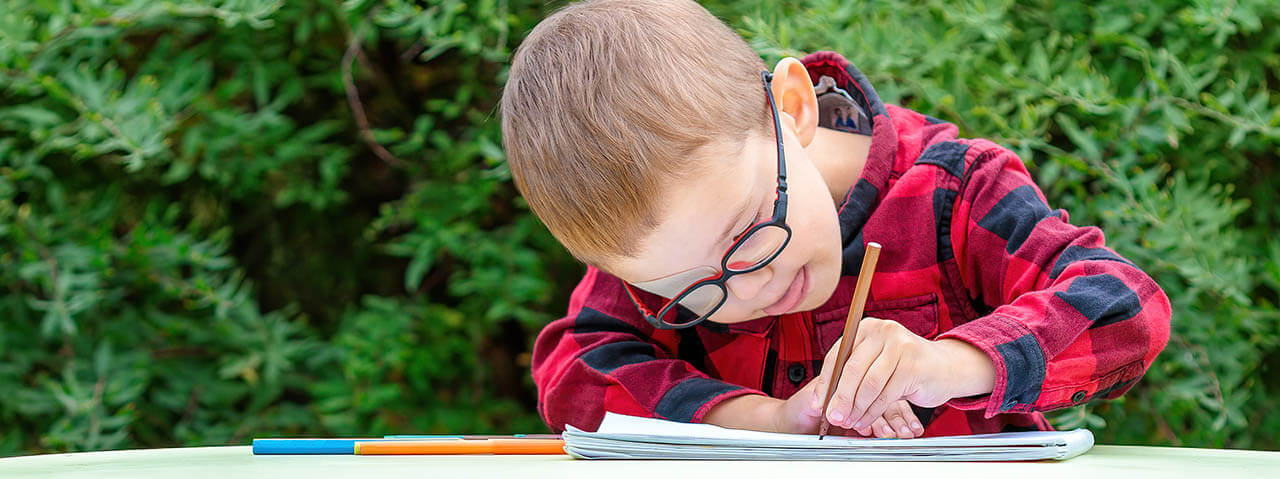 A Little Boy Draws In The Garden. He Wears Glasses And An Eye Pa