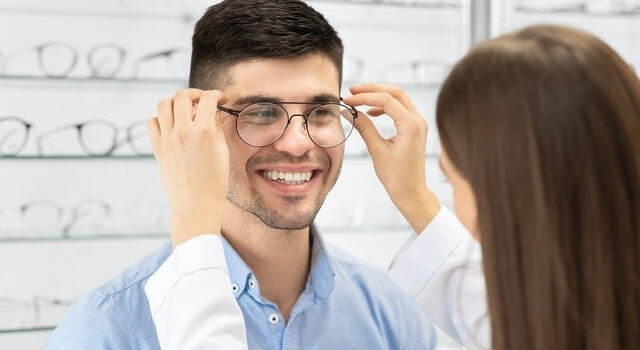Optical Shop. Female Optician In White Coat Helping Handsome Guy