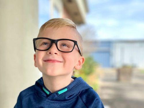 kid wearing eyeglasses winks