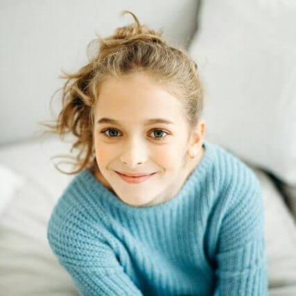 blonde woman smiling blue sweater 640px.jpg