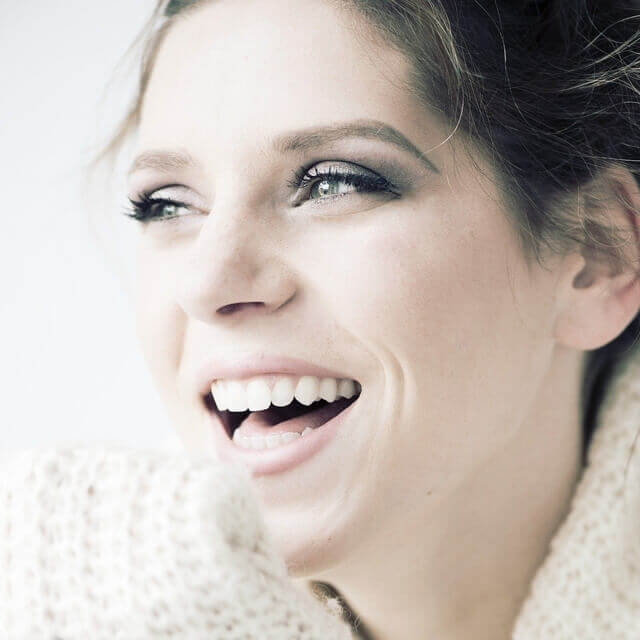 happy woman in white sweater 640 min