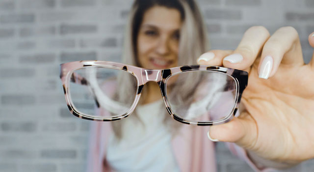 woman-in-the-background-holding-up-pink-tortoiseshell-glasses
