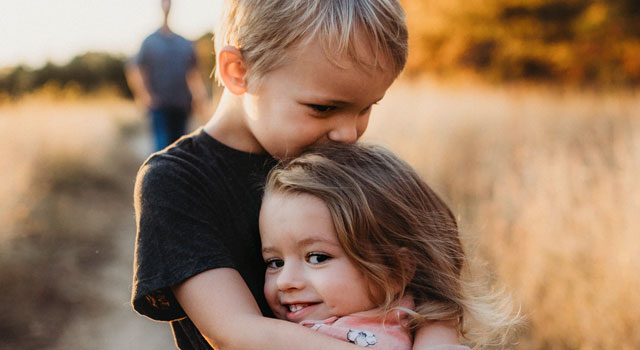 brother-and-sister-hugging-each-other-and-smiling
