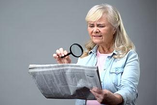 senior with magnifiying glass reading paper Thumbnail.jpg