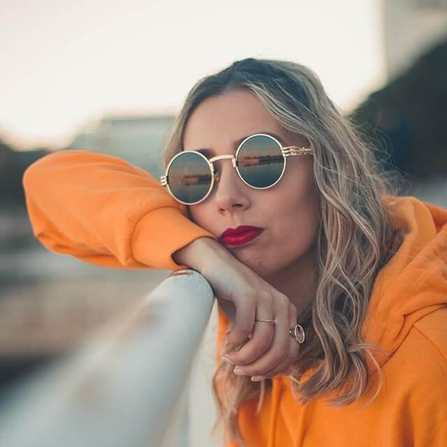 girl in orange sweater wearing eyeglass