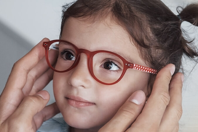 childrens eye exams young girl red glasses crop