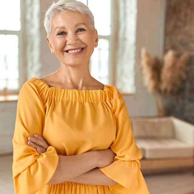Attractive confident mature blonde woman wearing yellow dress sq.jpeg