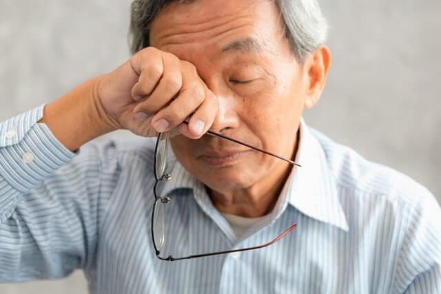 man rubbing his dry eyes