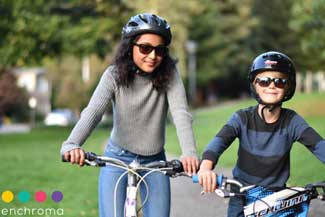 Happy mother and son riding bicycles and wearing Enchroma Glasses