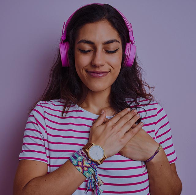 Young beautiful woman listening to music using headphones over i