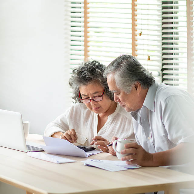 Stressed Asian Senior Couple Using Calculator And Calculate Fami