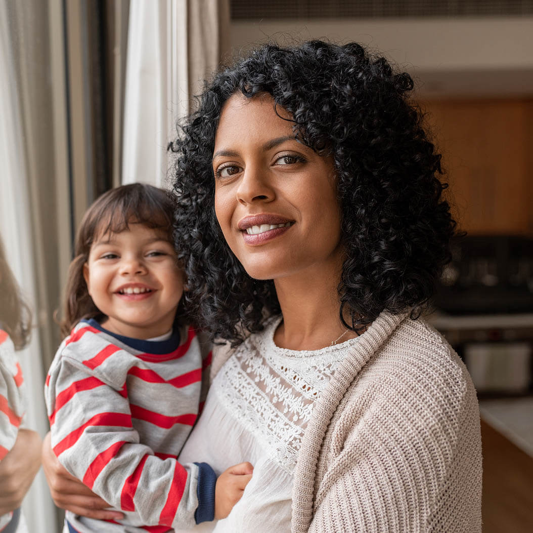 Smiling Mother And Daughter Standing By Their Living Room Window