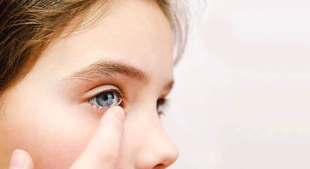 Girl inserting contact lens in San Jose, California