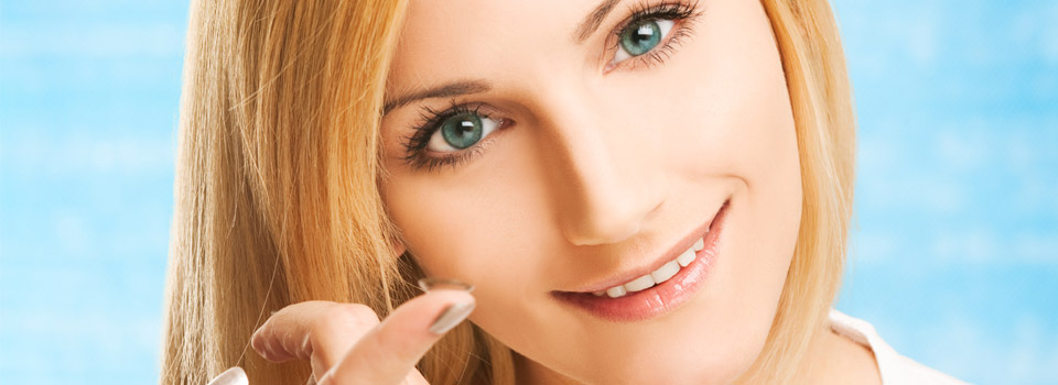 Blonde woman holding a contact lens on her finger