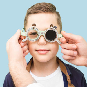 close up of young boy covering one eye in front of eye chart