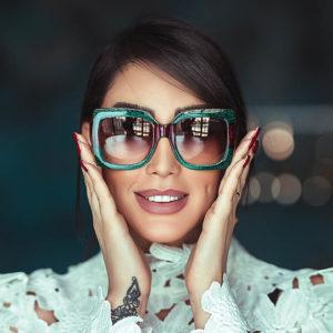 blue glasses on brunette smiling woman