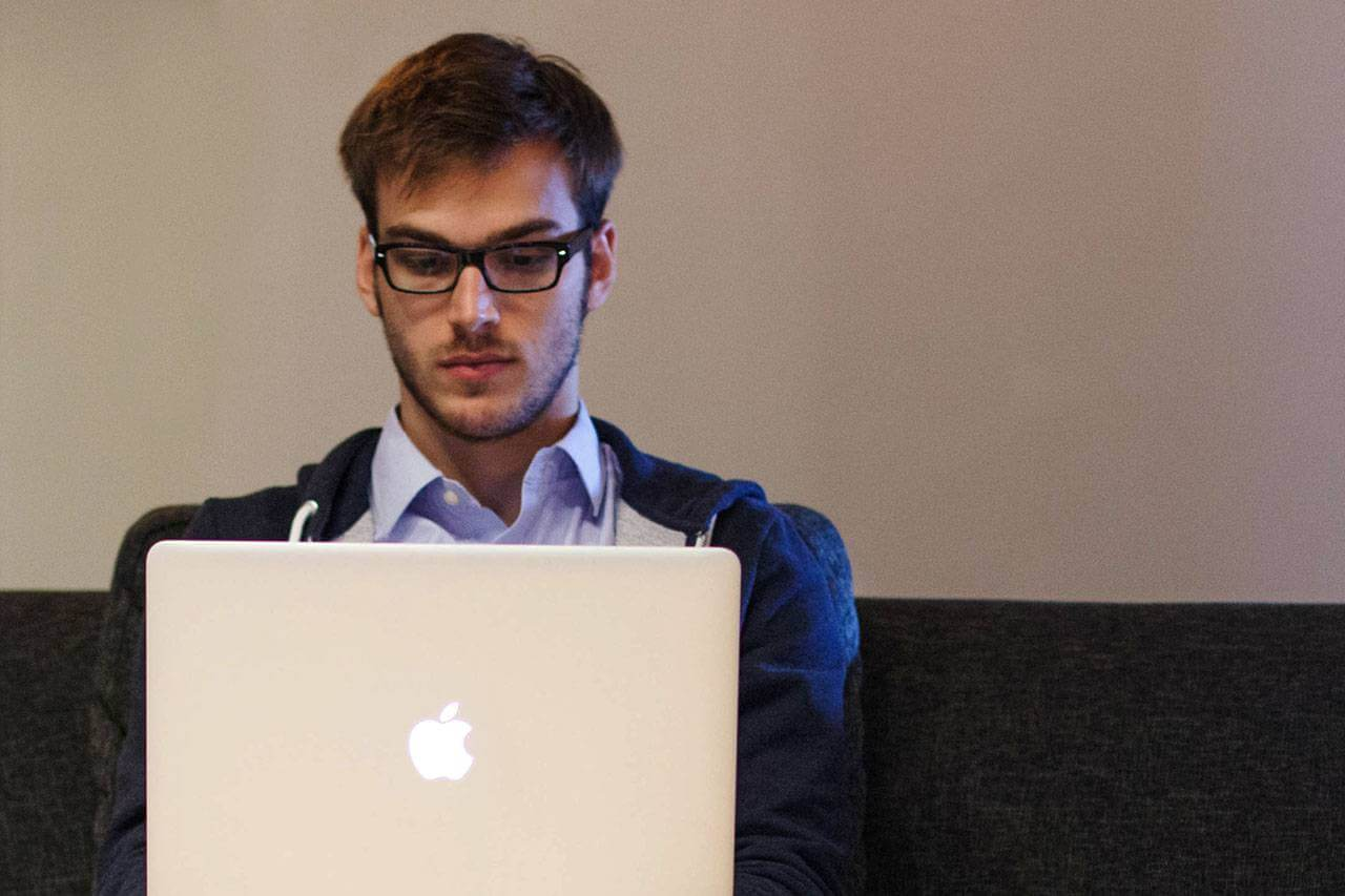 Young Man Using Laptop 1280x853