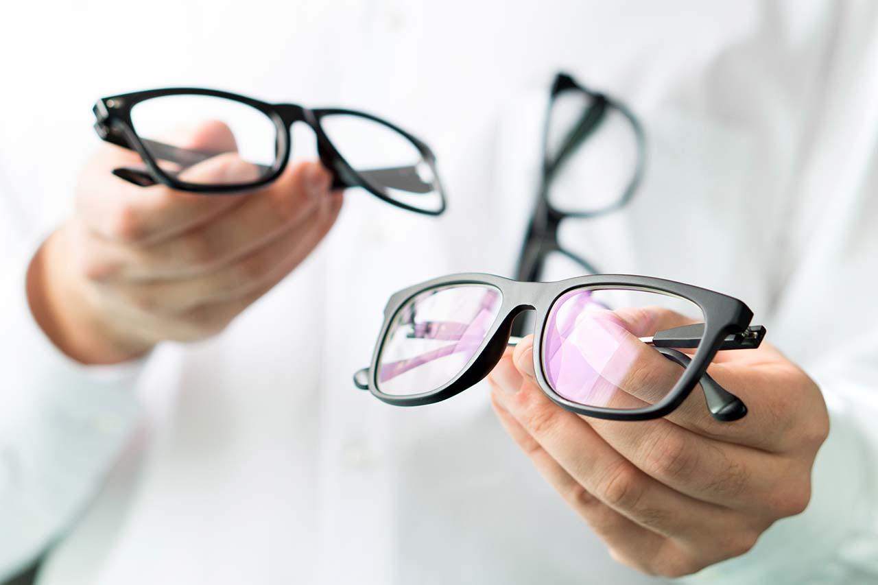 optician holding eyeglasses near you