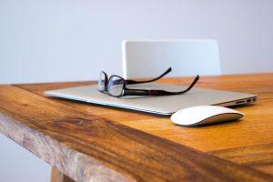 Eyeglasses sitting on top of laptops