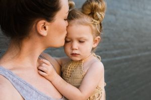 Woman kissing her young daughter