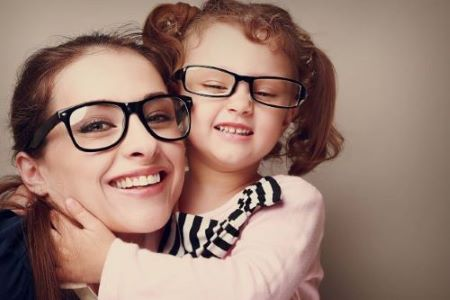 sisters with glasses smiling