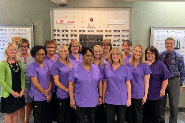 Our eye doctors and eye care staff in front of the optical display, in Hemlock, MI