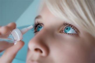 woman applying eyedroppers, close up in Saginaw, MI