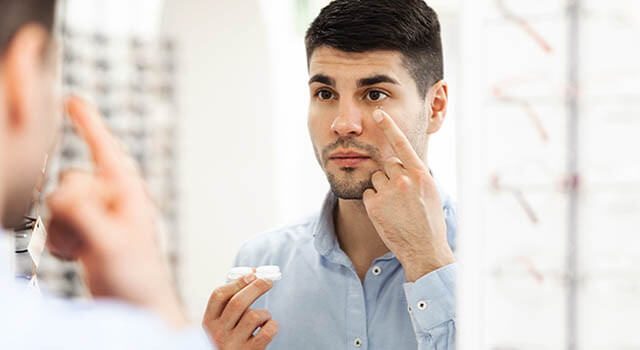 man holding up contact lens near his eye